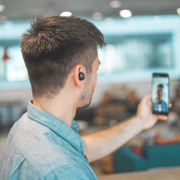 mężczyzna stoi tyłem i trzyma w ręce telefon, w uszach ma słuchawki);