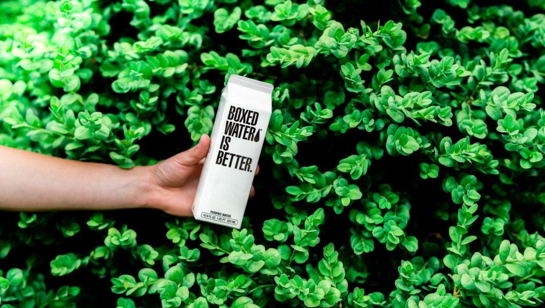 tło z parkanu, ręka trzyma biały karton z napisem boxed water is better);