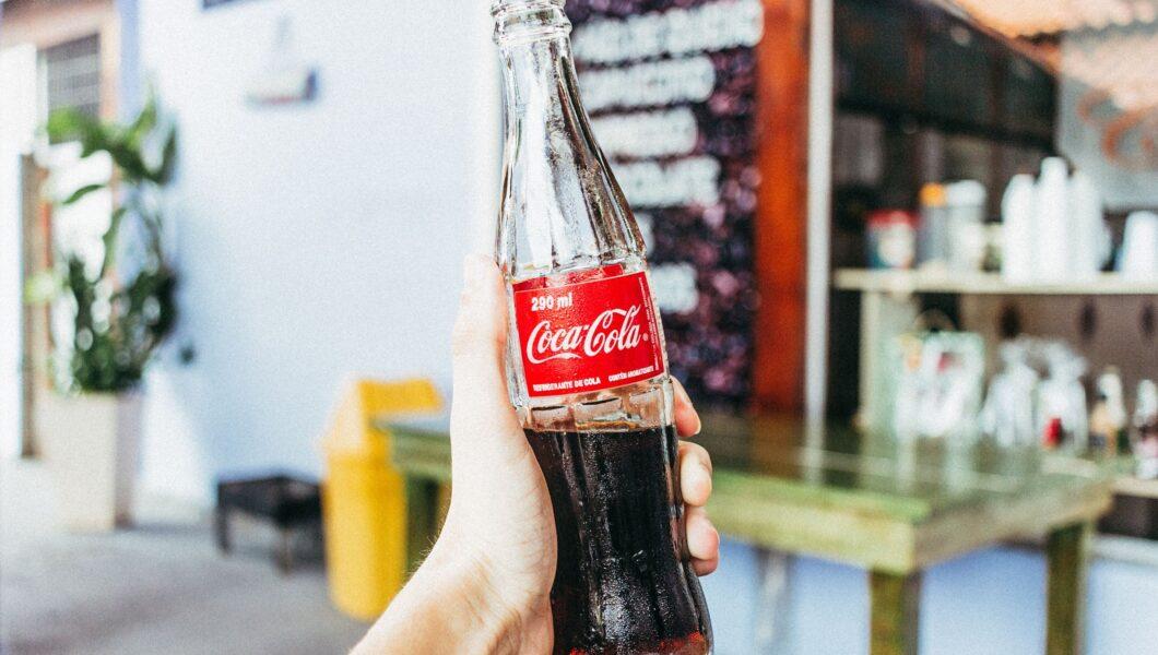 ręka trzymająca butelkę coli);