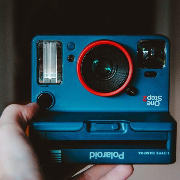 ręka trzymająca niebieski polaroid z czerwoną obwódką obiektywu);